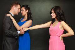 Couple and his jealous woman lover. Love triangle concept. Man cheating on his wife, looking and touching other woman, choosing between two ladies Stock Photography