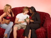 Love triangle drama of two girls and one guy. Young beautiful ethnic woman tries to seduce young Caucasian man holding red rose while his girlfriend Royalty Free Stock Images