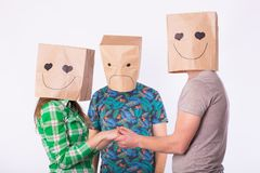 Love triangle, jealousy and unrequited love concept - woman and man with bags over heads holding hands and another man Royalty Free Stock Photos