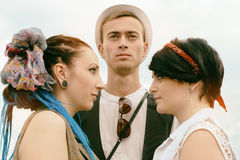 Love triangle young guy before a choice in resistance of two gir Royalty Free Stock Photo