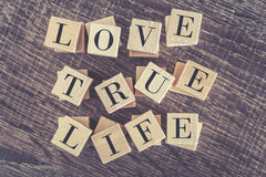 Love True Life message formed with wooden blocks. On a wooden table royalty free stock photos
