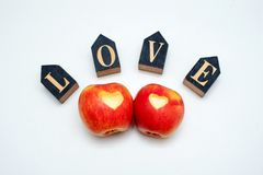 Love of two apples concept with a neatly incised heart in the skin of a ripe red apple on white table stock images