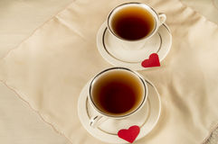 Love. Two cups of tea and red hearts Stock Photography
