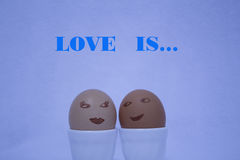 Love is... Two painted eggs like faces of a girl and a guy on the blue background Stock Images