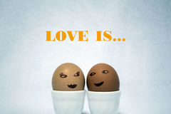 Love is... Two painted eggs like faces of a girl and a guy on the white background Royalty Free Stock Image