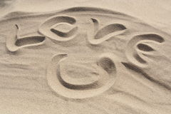 Love U. Writing on the sand Stock Photo