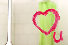 Love u on mirror. A heart drawn on a mirror with lipstick Stock Photography