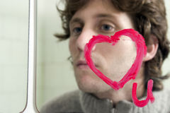 Love u on mirror with man in background. A heart drawn on a mirror with lipstick with a guy looking at the mirror Royalty Free Stock Image