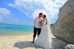 Love umbrella - newlyweds couple on exotic beach. Young bride and groom on a tropical beach under the sun umbrella Royalty Free Stock Image