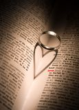 Love, the universal language. A platinum ring casts a heart-shaped shadow in a book with the word 'love' highlighted in red Royalty Free Stock Photo