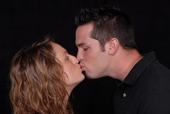Love up close and kissing. Close up of young woman and man caught kissing in front of a black back ground Royalty Free Stock Photo
