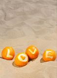 Love and vacation concept - the carved inscription love on oranges, lying on the sand Royalty Free Stock Photo