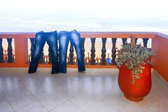 Love is on vacation. Wet men`s and women`s jeans dry on the balcony. Conceptual photo. Love is on vacation. Wet men`s and women`s jeans dry on the balcony Royalty Free Stock Photos