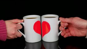 Love or Valentine's day celebration concept. Cups (with halves of the heart) put near to make one painted heart stock video