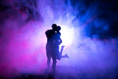 Love Valentine`s Day concept.Sillhouette of sweet young couple in love standing in the field and hugging on dark toned foggy backg. Round. Decoration with doll Royalty Free Stock Photography
