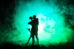 Love Valentine`s Day concept.Sillhouette of sweet young couple in love standing in the field and hugging on dark toned foggy backg. Round. Decoration with doll Royalty Free Stock Images