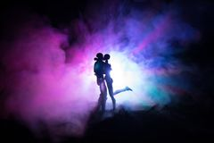 Love Valentine`s Day concept.Sillhouette of sweet young couple in love standing in the field and hugging on dark toned foggy backg. Round. Decoration with doll Royalty Free Stock Image