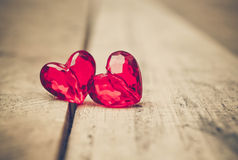 Love for Valentine`s day. Two red beads with a shape of a heart on wood plank floor royalty free stock photo