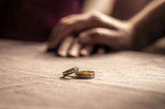 Love, Valentine`s day and wedding concept. Two wedding rings with man and woman hands blurred in the background. Selective focus. Love, Valentine`s day and Royalty Free Stock Photos