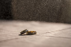 Love, Valentine`s day and wedding concept. Two wedding rings with man and woman hands blurred in the background. Selective focus Royalty Free Stock Photos