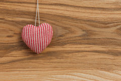 Love Valentine's heart hanging on wooden texture background Royalty Free Stock Photo