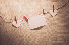 Love Valentine's hearts natural cord and red clips hanging. Love Valentine's hearts and card natural cord and red clips hanging on sackcloth texture background Stock Images