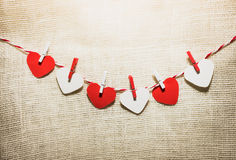 Love Valentine's hearts natural cord and red clips hanging Stock Photo