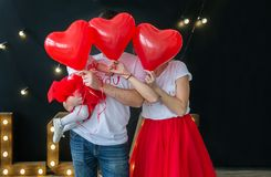 Love and Valentines day. Caucasian family hiding faces behind red heart shaped balloons. Black studio background. Horizontal family portrait royalty free stock images