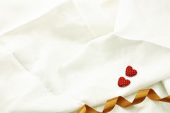 Love Valentines Day red heart on off white linen fabric backgrou. Valentines day background with two hearts on linen fabric background and gold ribbon Royalty Free Stock Photography