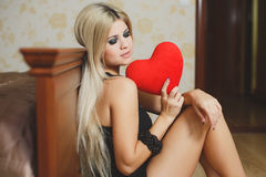 Love and valentines day woman holding heart sitting on the floor in a bedroom. Beautiful blonde woman in love. Portrait of a beautiful young smiling woman with Stock Photos