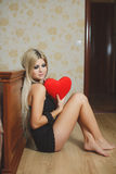 Love and valentines day woman holding heart sitting on the floor in a bedroom. Beautiful blonde woman in love. Portrait of a beautiful young smiling woman with Royalty Free Stock Photos