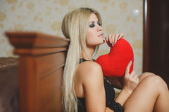 Love and valentines day woman holding heart sitting on the floor in a bedroom. Beautiful blonde woman in love. Portrait of a beautiful young smiling woman with Stock Photo