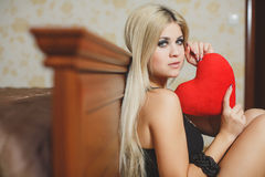 Love and valentines day woman holding heart sitting on the floor in a bedroom. Beautiful blonde woman in love. Stock Photography