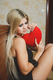 Love and valentines day woman holding heart sitting on the floor in a bedroom. Beautiful blonde woman in love. Royalty Free Stock Image