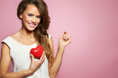 Love and valentines day woman holding heart smiling cute and adorable isolated on pink background. Beautiful ethnic caucasian woma Stock Photos