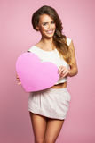 Love and valentines day woman holding heart smiling cute and adorable isolated on pink background Stock Image