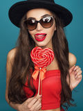 Love and valentines day, woman with sly smile holding heart. Portrait of Beautiful woman in hat with bright makeup and red heart in hand Stock Photo