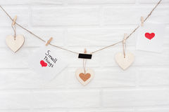 Love valentines garland with brick wall on a background. Wise phrase `small things` Stock Images