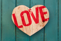Love Valentines message wooden heart on turquoise painted backgr Royalty Free Stock Images