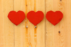 Love Valentines red cardboard hearts on rough pine background Royalty Free Stock Image