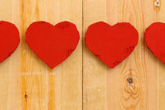 Love Valentines red cardboard hearts on rough pine background Royalty Free Stock Images