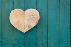 Love Valentines wooden heart on turquoise painted background Stock Photo