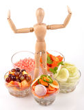 Love vegetarian. Wooden mannequin chef making a salad Stock Photos