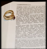 Love verse with rings. Bible open to love verse in corinthians with wedding rings Royalty Free Stock Images