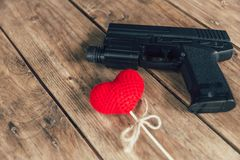 Love and violence concept: pistol gun and love red heart on wood. Pistol gun and love red heart on wood background stock images
