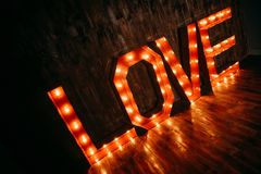 LOVE volume retro letters glowing with light bulbs. On a wooden background Royalty Free Stock Photography
