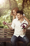 Love and wedding concept. Young happy couple sitting in the park. And smiling. Man holding in is hands red box with ring and making propose to woman Stock Images