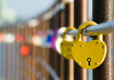 Love wedding locks are in a row. Yellow wedding lock in the focus and the other are blurred Royalty Free Stock Photos