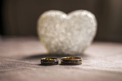 Love, wedding and Valentine`s day concept. Beautiful golden wedding rings and glass heart selective focus. useful as greeting card Royalty Free Stock Image