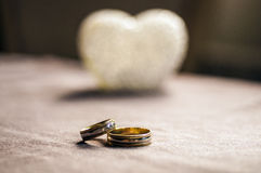 Love, wedding and Valentine`s day concept. Beautiful golden wedding rings and glass heart selective focus. useful as greeting card Stock Image
